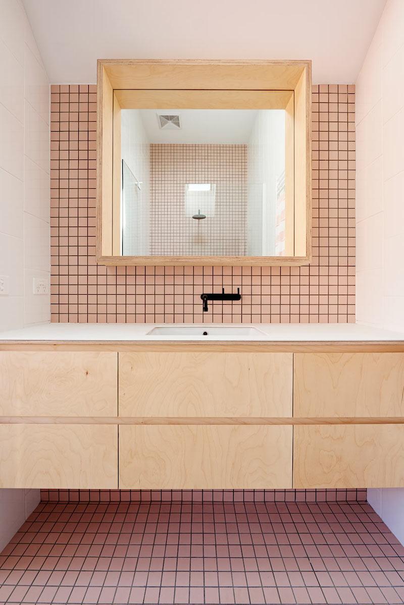 Original cuarto de bano con grifo negro, mobiliario madera natural y azulejos en color rosa