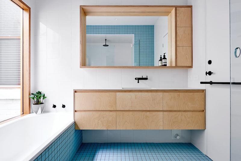 cuarto de bano mobiliario de madera, griferia en negro y azulejos de color rosa y azul
