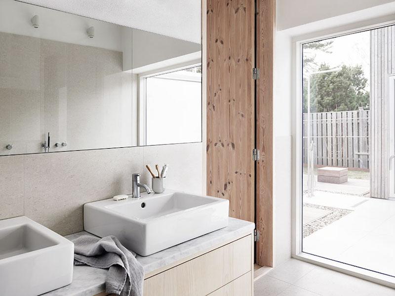 cuarto de bano casa de campo con encimera de marmol y puertas de madera natural veteada