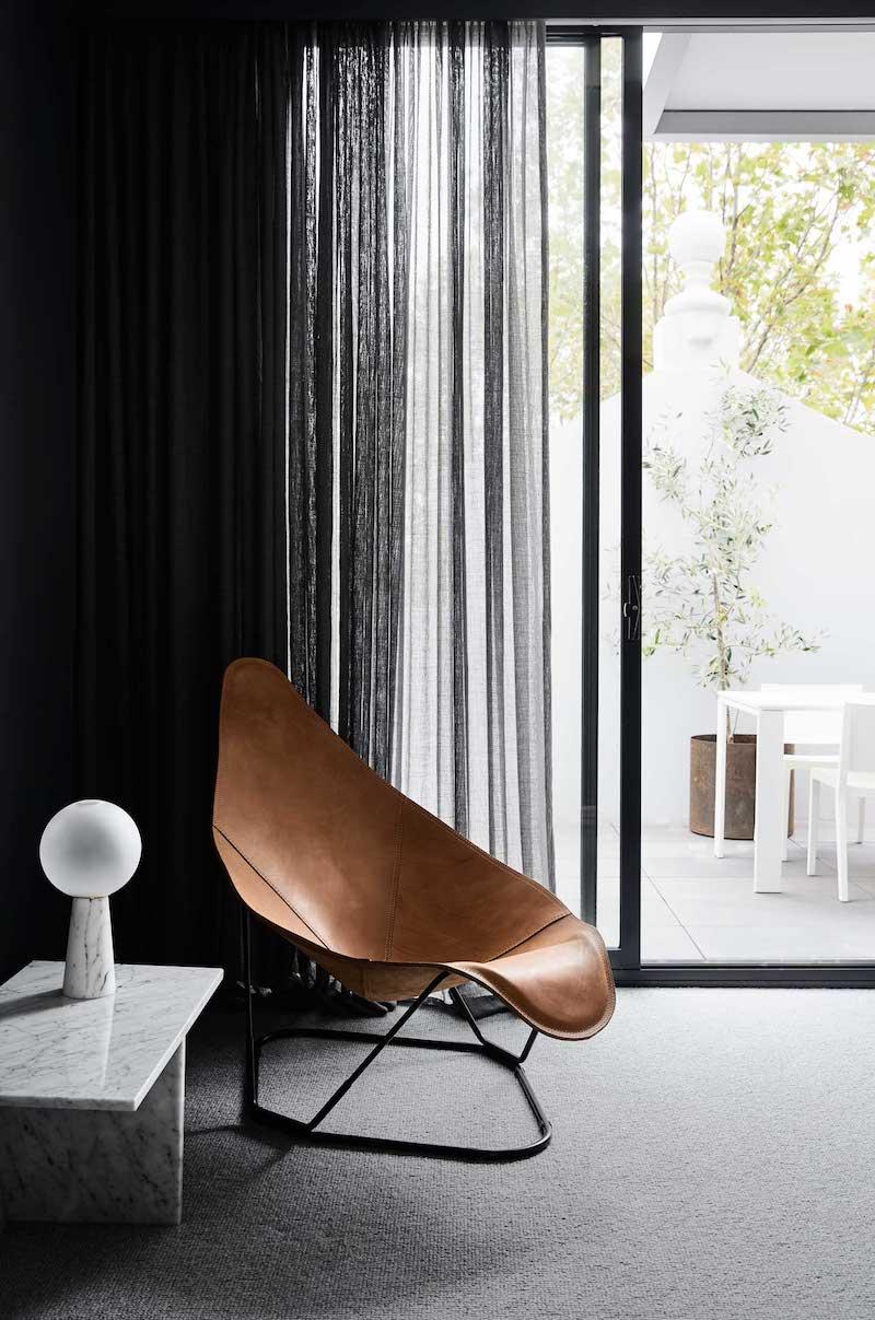 Un hogar sobrio y minimalista con suelos de madera mobiliario gris y cortinas oscuras negro 5