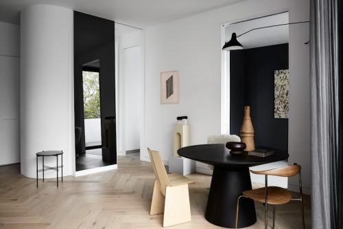 Un hogar sobrio y minimalista con suelos de madera mobiliario gris y cortinas oscuras negro