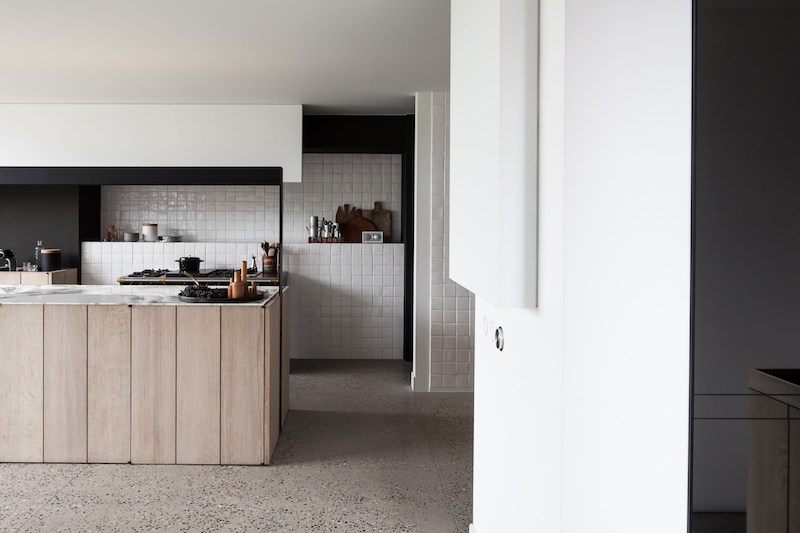 Una cocina minimalista en marmo baldosas cuadriculadasl y madera en una antiguo granero reformado en belgica 3