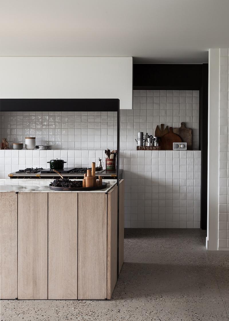 Una cocina minimalista en marmo baldosas cuadriculadasl y madera en una antiguo granero reformado en belgica