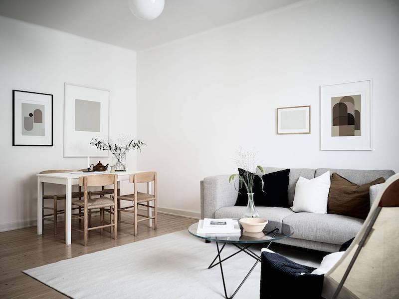 Ultima tendencia decoracion salon sobrio mucha madera y tejidos grises tapizado sofa cuadros dibujos abtracto 2