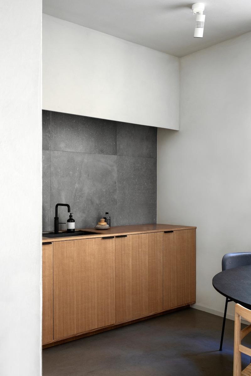cocina mobiliario madera griferia negra baldosas acabado cemento pulido, decoracion proyecto por Norm Architects 4